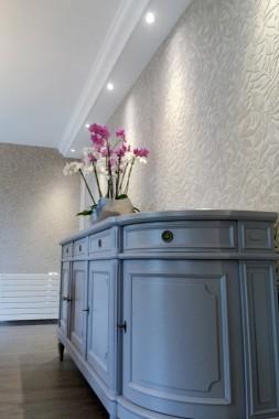 Détail sur meuble buffet peint. Tapisserie velours avec motif floral.